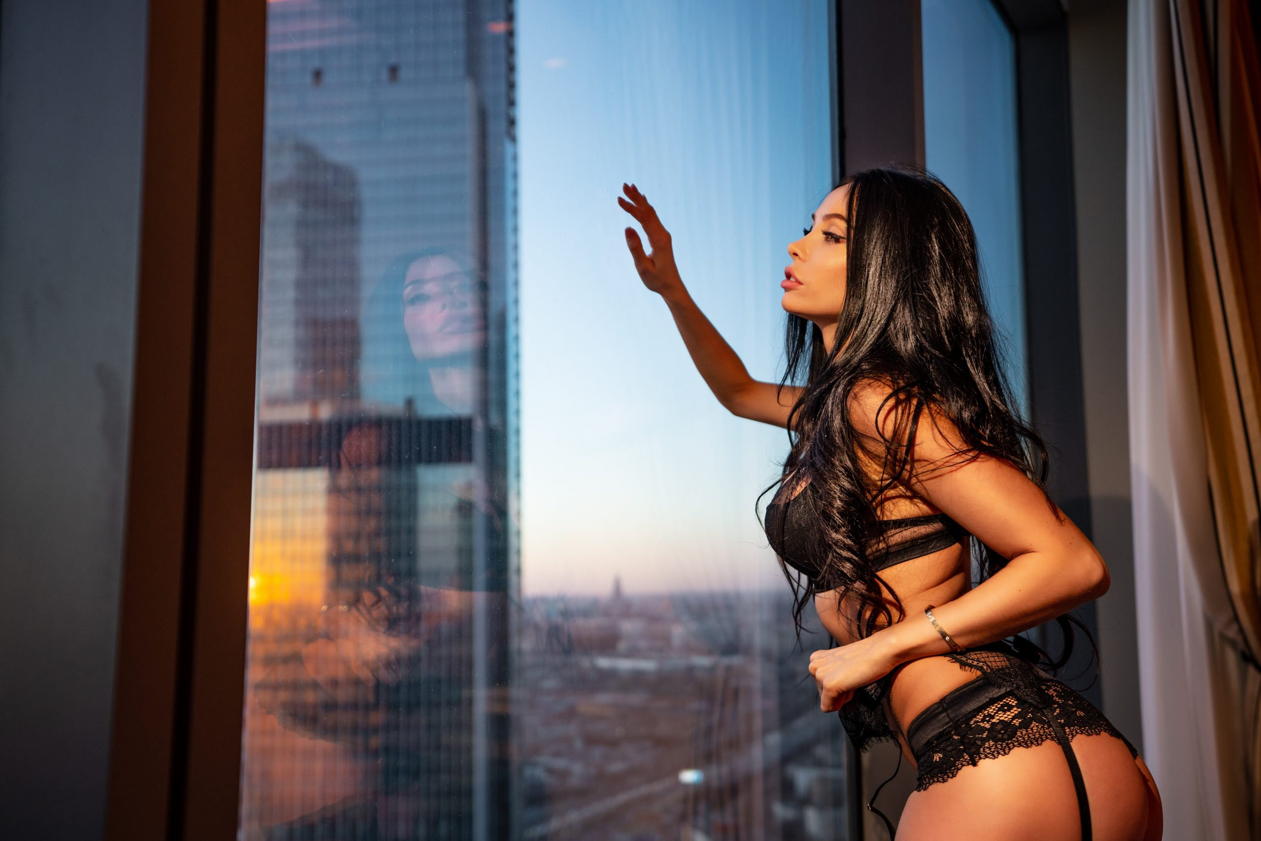 Young sexy girl in lingerie by the window in the apartment